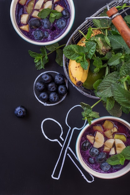 Bowl of smoothies with berries on a chalkboard with spoons Premium Photo