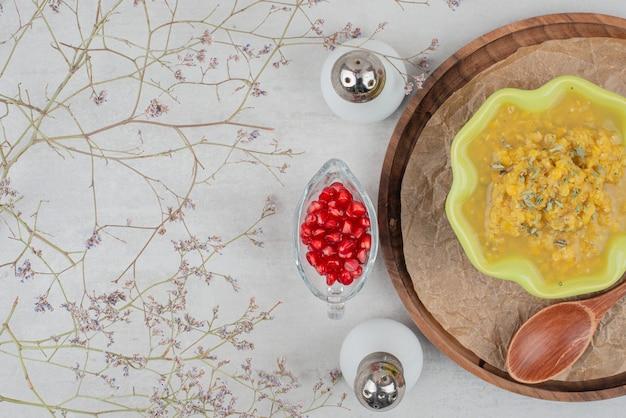 Ciotola di minestra, sale e semi di melograno sulla superficie bianca. Foto Gratuite