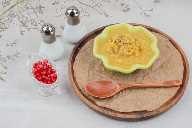 Ciotola di zuppa sul piatto di legno con sale e semi di melograno. Foto Gratuite