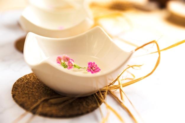 Bowl of spa massage oil on coaster Free Photo