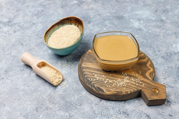 Bowl of tahini with sesame seeds on concrete surface Free Photo