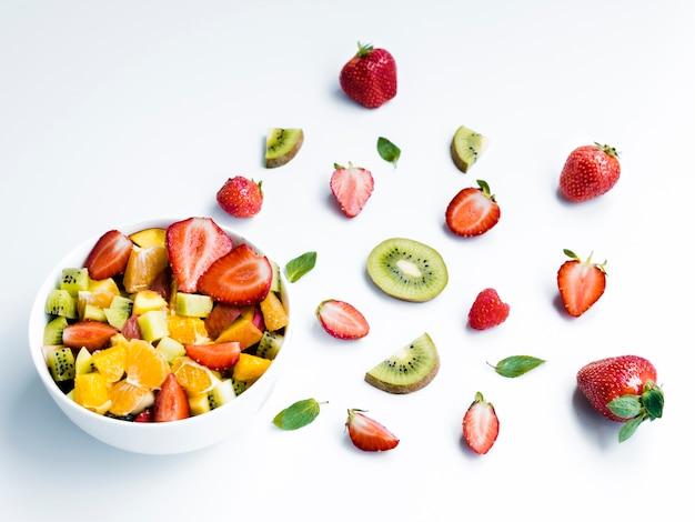 Bowl of tasty fruit salad near pieces of strawberry and kiwi on white background Free Photo