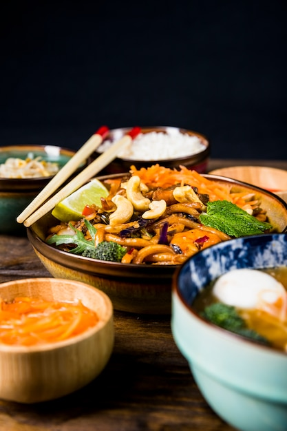 Bowl of thai udon noodles with nuts; broccoli; lemon and mint toppings Free Photo