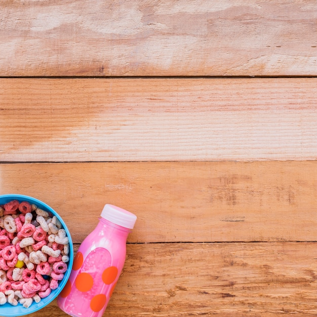 Bowl with cereals and pink milk bottle Free Photo