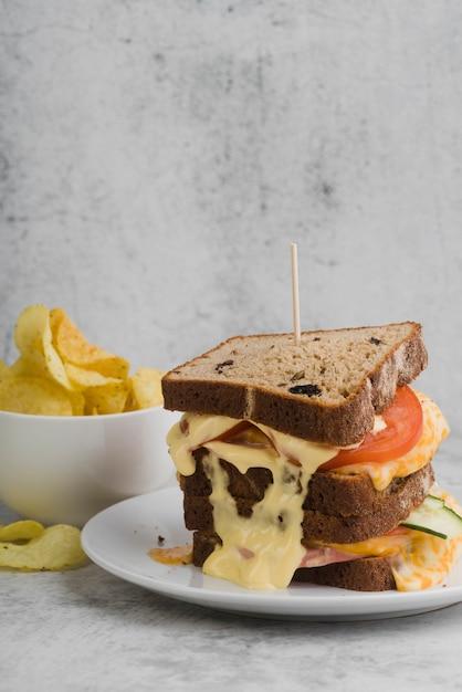 サンドイッチの横にあるチップのボウル 無料写真