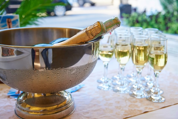 A bowl with cold champagne on the table with filled glasses. Premium Photo