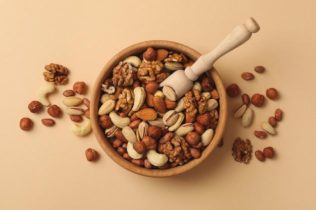 Чаша с разными орехами и деревянной ложкой на бежевом фоне Premium Фотографии