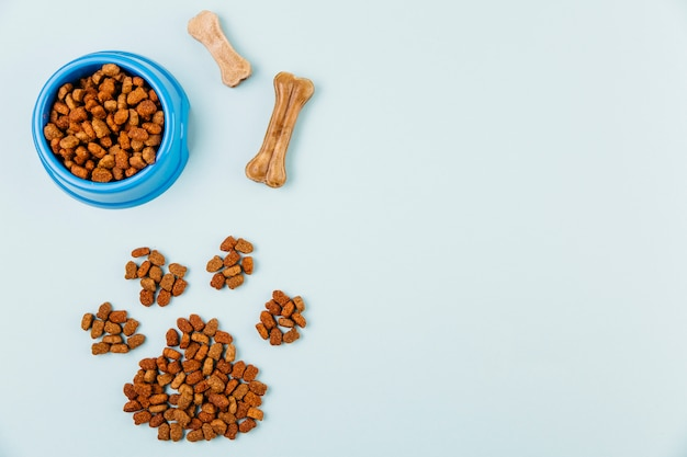Bowl with feed and paw figure on light background Free Photo