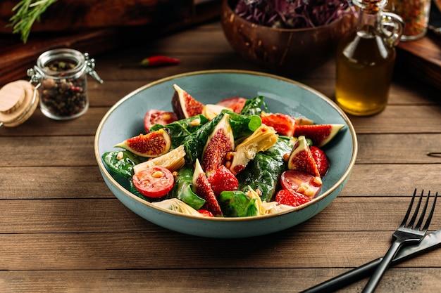 Миска с инжиром и овощным салатом Premium Фотографии
