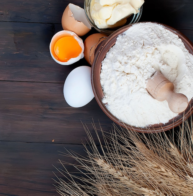 Bowl with flour eggs ears of wheat and butter on vintage wooden board food and drink concept Premium Photo