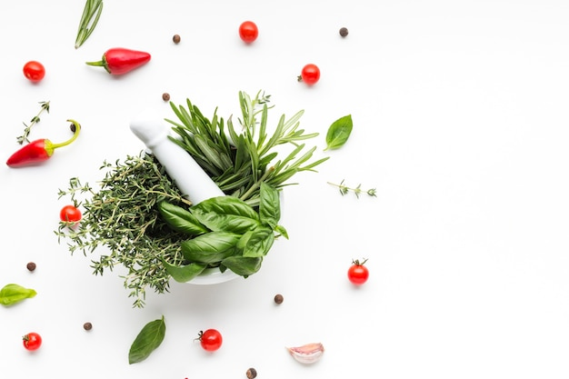 Bowl with herbs surrounded by vegetables Free Photo