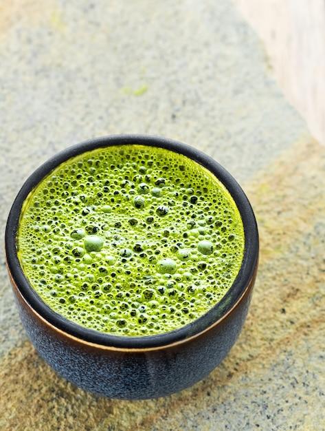 灰色の石の表面に泡の抹茶緑茶を入れたボウル 無料写真