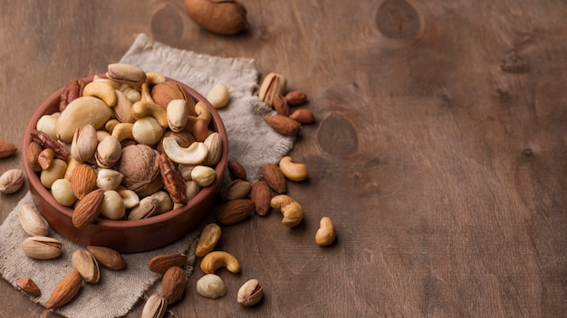 Bowl with nuts copy space wooden background Free Photo