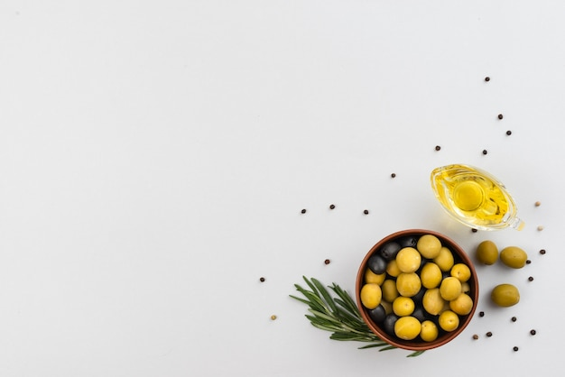 Bowl with olives and cup with oil olives on table Free Photo