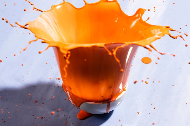 Bowl with orange paint and violet background Free Photo