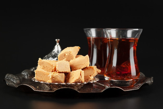 Bowl with pieces of turkish delight lokum and black tea Premium Photo