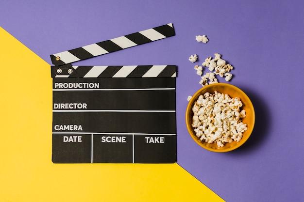 Ciotola con popcorn accanto all'ardesia di film Foto Gratuite
