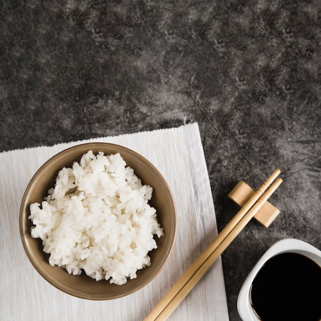 Bowl with rice on napkin near chopsticks and soy sauce Free Photo