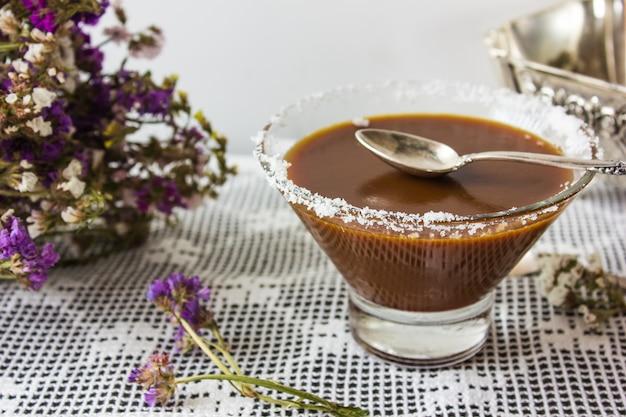 Чаша с соленой карамелью и конфеты на деревянном фоне, вид сверху Premium Фотографии