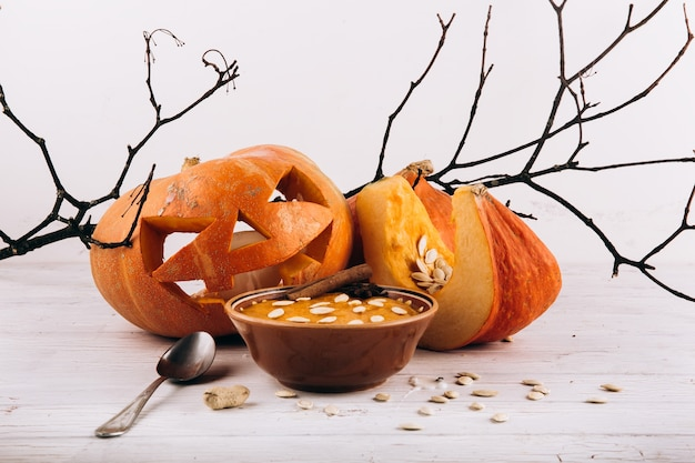 Чаша с супом стоит перед сухарями хэллоуина на столе Бесплатные Фотографии