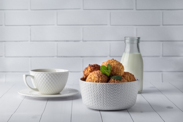 Bowl with tasty coconut cookies and drinks on white wooden table Premium Photo