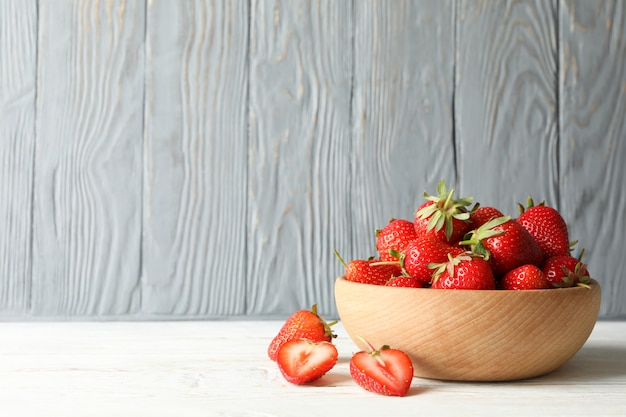 Bowl with tasty strawberry on wooden table. summer berry Premium Photo