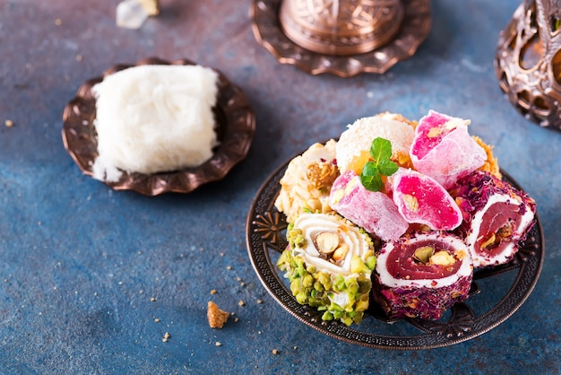 Bowl with various pieces of turkish delight lokum and black tea with mint Premium Photo