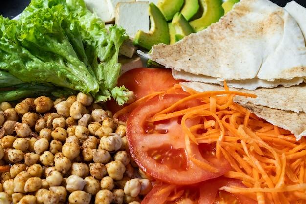 素朴なテーブルの上の仏bowlのクローズアップビュー。ひよこ豆、サラダ、野菜、豆腐、ピタパン、アボカドの完全菜食 Premium写真