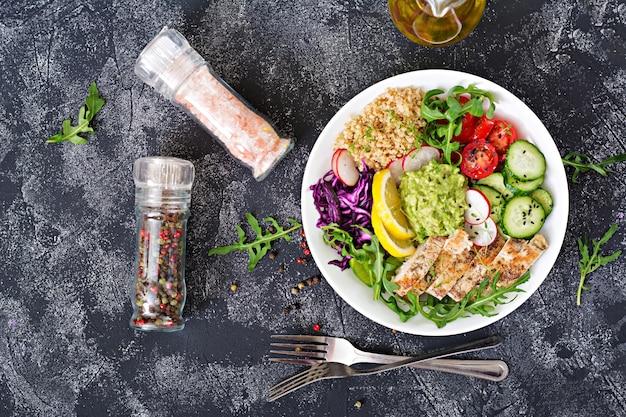 健康的な夕食。グリルチキンとキノア、トマト、ワカモレ、赤キャベツ、キュウリ、ルッコラとグレーのテーブルでの仏bowlランチ。平干し。上面図 Premium写真