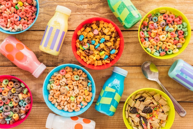 Bowls of cereals with milk bottles and spoon Free Photo
