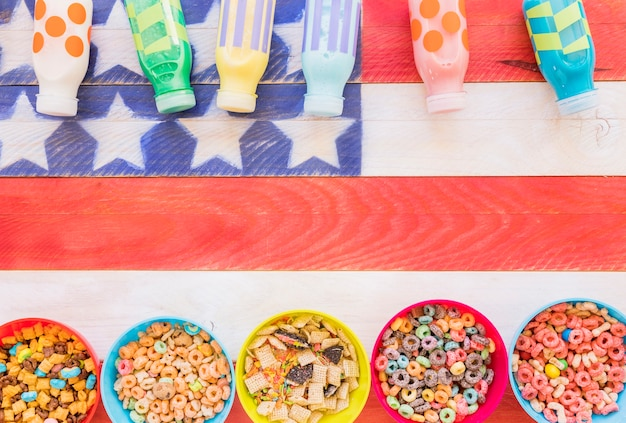 Bowls of cereals with milk bottles on table Free Photo
