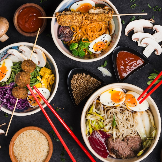 Bowls of noodles with eggs; vegetables and sauces on black background Free Photo