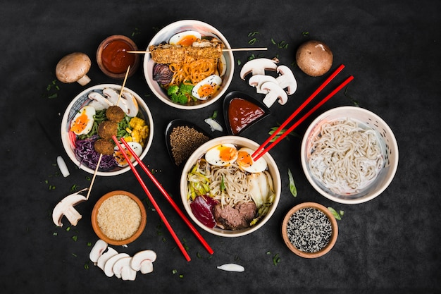 Bowls of noodles with ingredients and chopping sticks on black background Free Photo