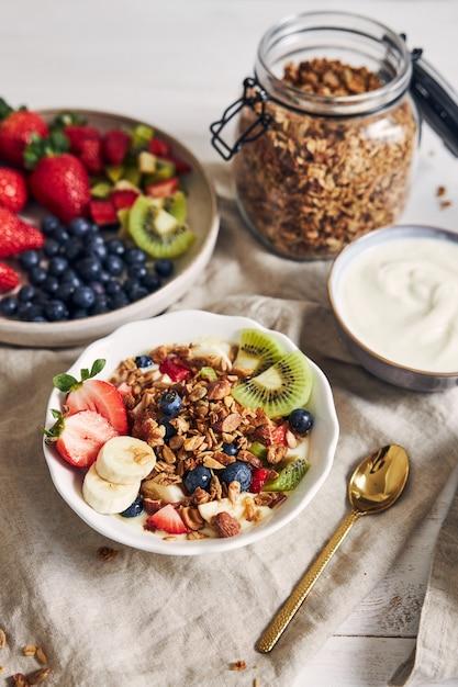 Чаши гранолы с йогуртом, фруктами и ягодами на белой поверхности Бесплатные Фотографии