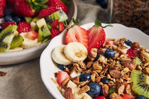 Миски мюсли с йогуртом, фруктами и ягодами на белой поверхности Бесплатные Фотографии