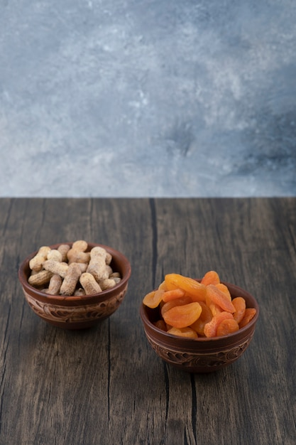 Чаши здоровых сушеных плодов абрикоса и арахиса в раковине на деревянном столе. Бесплатные Фотографии
