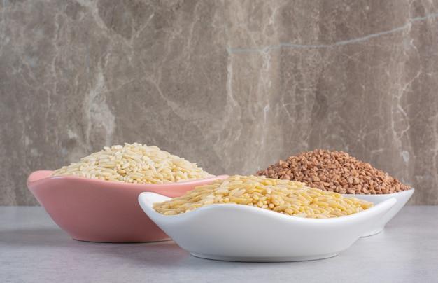 Ciotole di popcorn e fiocchi su marmo. Foto Gratuite
