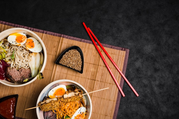 Bowls of ramen noodles with eggs and vegetables on chopsticks over the placemat against black background Free Photo