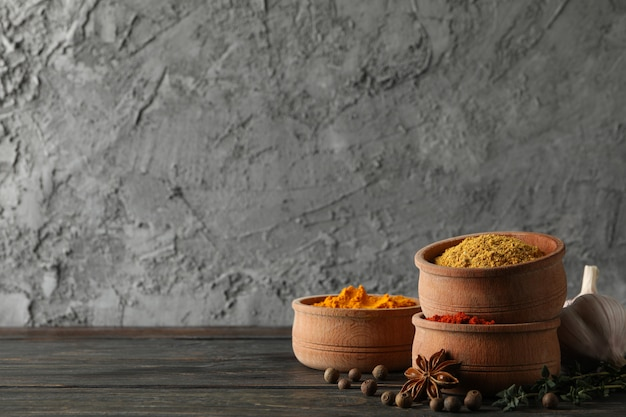 Bowls with different powder spices and ingredients on wooden background, space for text Premium Photo