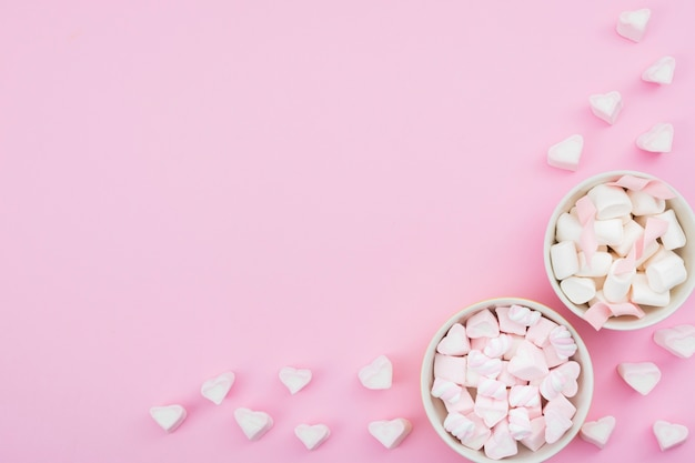 Bowls with meringue on pink background Free Photo