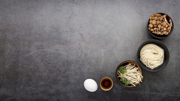 Bowls with noodles and mushrooms on a grey background Free Photo