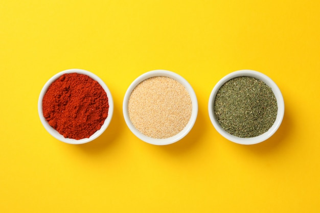 Bowls with red pepper, garlic and dill powder on yellow background, top view Premium Photo