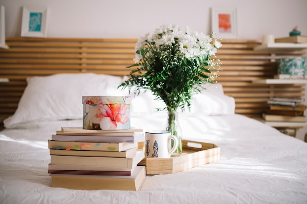Box on books near tray with bouquet Free Photo