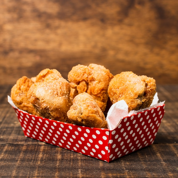 Box of fried chicken on wooden table Free Photo