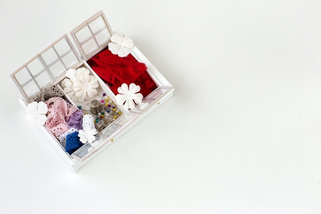 A box for handmade, there are ribbons of lace, needles, flowers Premium Photo