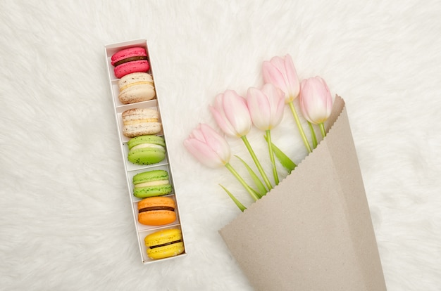 Box of multicolored macaroons and pink tulips on white fur, top view Premium Photo
