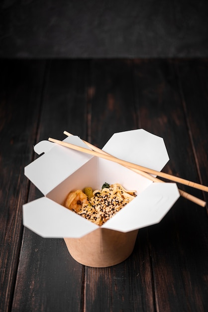 Box of of noodles with sesame seeds and chopsticks Free Photo