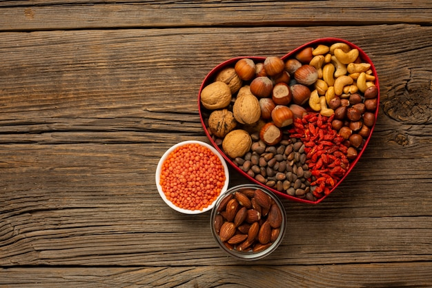 Box of nuts and spices on wooden table Free Photo