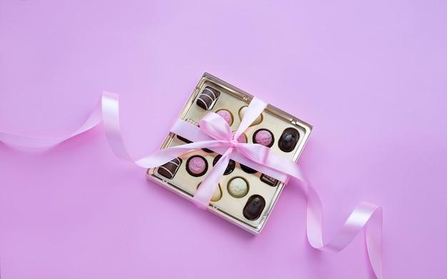 Коробка шоколадных конфет с розовым бантом на розовом фоне Premium Фотографии