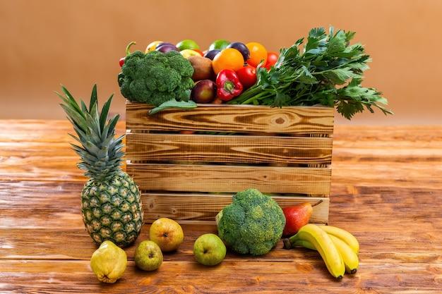 Коробка фруктов и овощей на деревянном столе Premium Фотографии